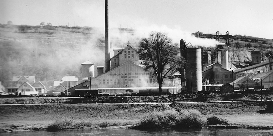 Historical photo: factory building with smokestacks wreathed in white smoke; the river Mosel in the foreground