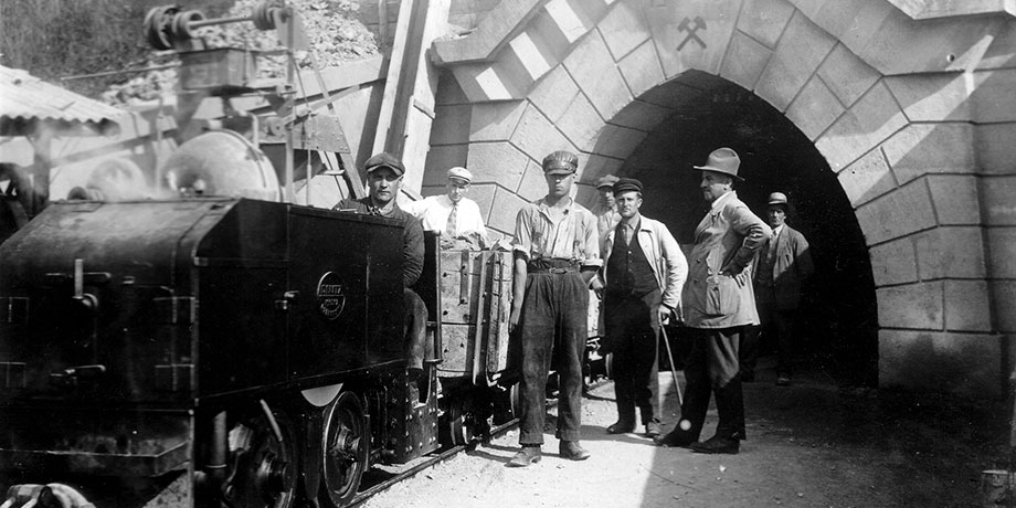 "Historical photo: Mine train and a group of miners pose in front of the entrance to an adit bearing the inscription ""Franz H. Hansen Stollen 1925""."